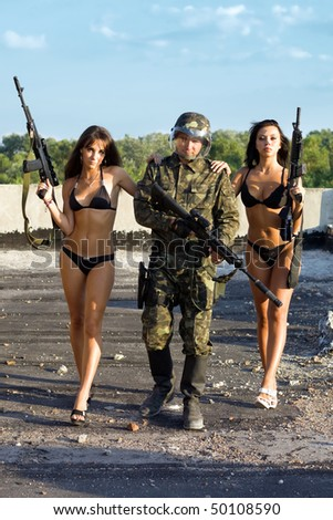 Two pretty women in underclothes leaning on soldier`s shoulders - stock photo