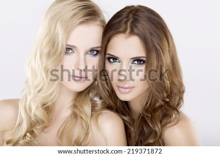Two pretty  young adult sensuality smiling attractive girl friends - Beautiful blond and brunette woman on white background - stock photo
