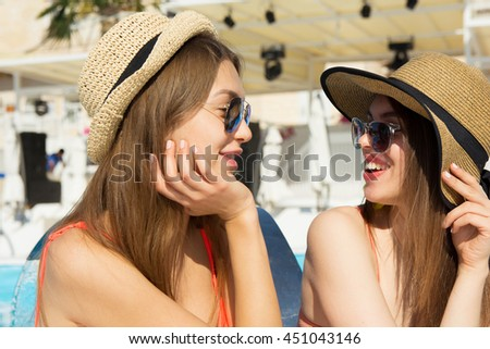 Two pretty young best friends sitting near swimming pool, enjoying summer, wearing trendy color swimwear and bright sunglasses
