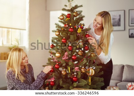 Two pretty young blond girlfriends or sisters decorating a Christmas tree with baubles and ornaments as they celebrate Christmas together at home - stock photo