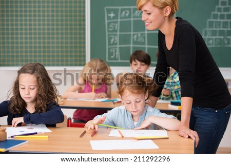 Two pretty young girls in class with their attractive female teacher sitting at their desk working on their class notes or project - stock photo