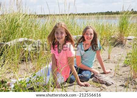 Two pretty young girls pose for a photo at the beach - stock photo