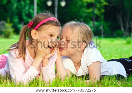 Two pretty young girls sharing a secret together - stock photo