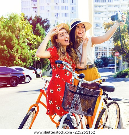 Two pretty young happy girls making selfie on retro camera, laughing going crazy and have great time, walking with vintage bikes in the city. Instagram bright colors. - stock photo