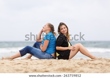 Two pretty young smiling woman sitting and relaxing on the sand on the seashore. Shallow depth of field. Focus on models. - stock photo