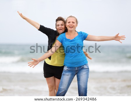 Two pretty young smiling women on the beach with open arms enjoying their freedom. Shallow depth of field. - stock photo