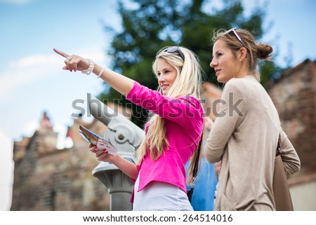Two pretty, young women sightseeing in Prague historic center - stock photo
