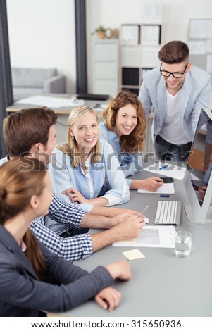 Two Pretty Young Women Smiling at Camera While in a Business Meeting Inside the Office.