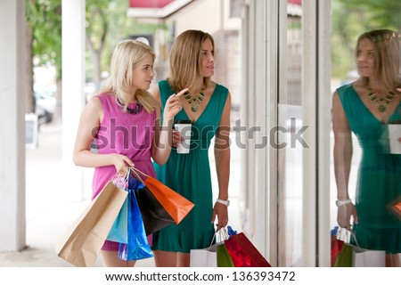 Two pretty young women window shopping downtown in a city.