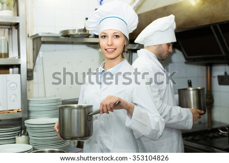 Two professional cooks working at restaurant kitchen