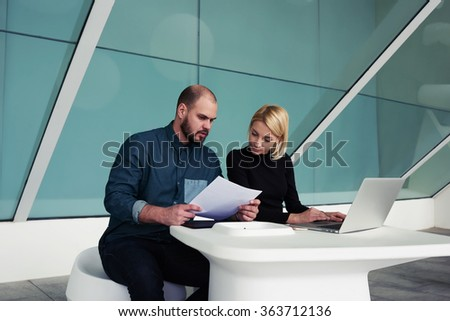 Two professional economists using paper documents and laptop computer for checking monthly report, man and woman entrepreneurs working together on portable net-book in modern office interior - stock photo