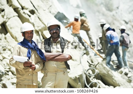 Two professional indian asian engineer builders foremans with plan at mountains construction site - stock photo