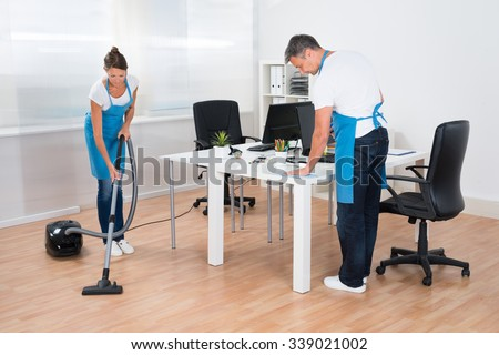 Two Professional Janitors Are Cleaning The Modern Office - stock photo