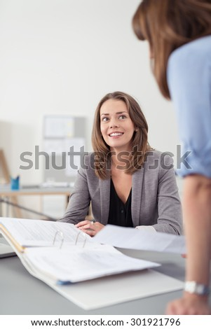 Two Professional Women Talking at the Table Inside the Office About the Business Documents in a Folder. - stock photo