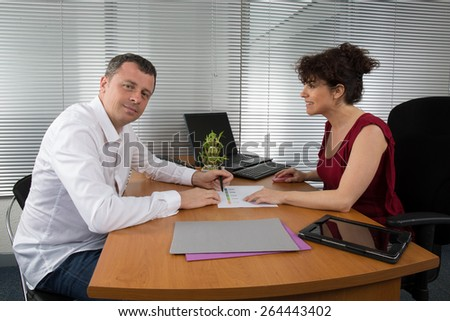 Two professionals holding a meeting to draw up the results of the financial period - stock photo