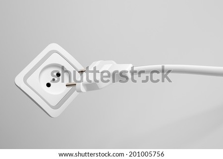 Two prong plug, cord and electrical power outlet providing a supply of domestic electricity on a grey wall, not plugged in - stock photo