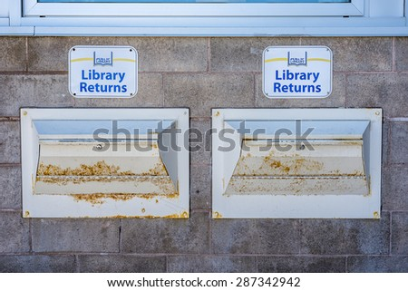 Two Public Library returns signs with the chutes below.  - stock photo
