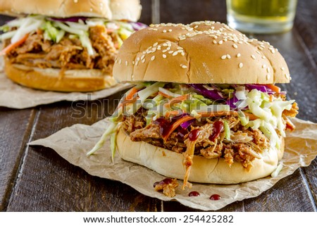 Two pulled pork barbeque sandwiches with coleslaw sitting on wooden table with glass of beer - stock photo