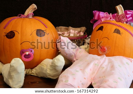 Two pumpkins dressed up as princess babies with pacifiers. - stock photo