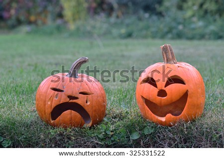 Two pumpkins in the grass  /  Two pumpkins in the grass, one laughing and one crying