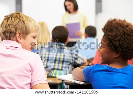 Two Pupils Talking In Class Together - stock photo