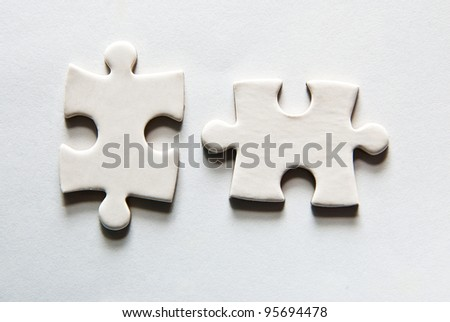 two puzzle pieces on a grey background - stock photo