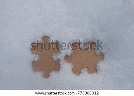 two puzzles. snowy background. concept of winter. imprint in the snow. snow background connect jigsaw puzzle pieces. photo for design.