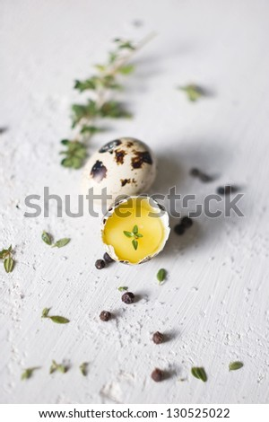 Two quail eggs with thyme - stock photo