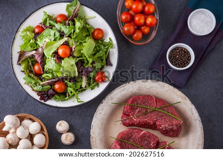 Two raw fillet steaks with a green salad, cherry tomatoes, mushrooms, salt and pepper on a slate background