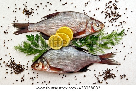 Two raw fresh fishes on marble table with lemon, pepper, dill and parsley. Crucian fishes. top view, flat lay. - stock photo