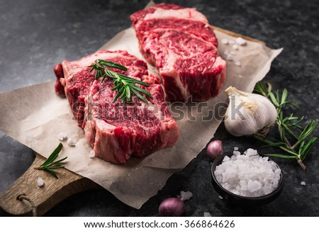 Two raw fresh marbled meat black angus steak ribeye, garlic, salt and  on dark background - stock photo
