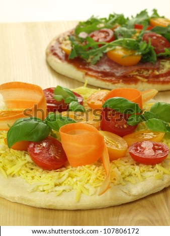 Two raw pizzas with ingredients prepared for baking - stock photo
