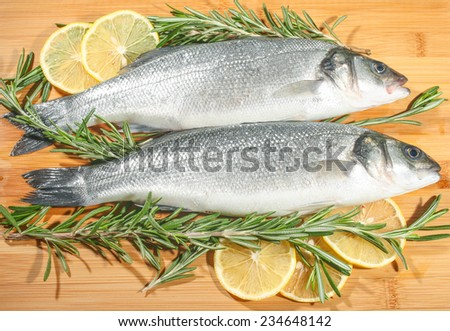 Two raw seabass with lemon and rosemary on the wooden background - stock photo