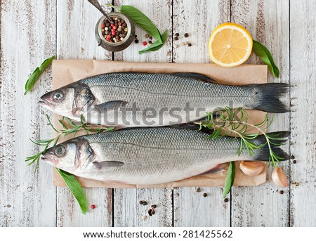 Two raw seabass with spices on an old wooden background. Top view - stock photo