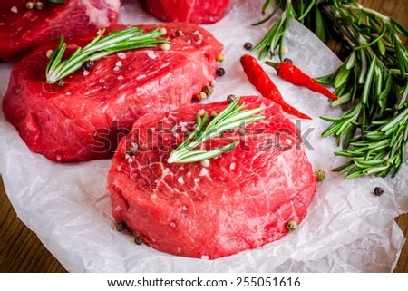 two raw steaks with rosemary, garlic, salt and pepper closeup - stock photo