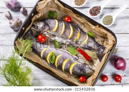 two raw trouts fish on the baking dish with cherry tomatoes, fennel, garlic, onion and spices, view from above - stock photo