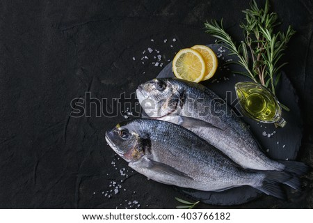 Two ready to cook raw bream fish with herbs, lemon and olive oil on stone slate board over black textured background. With copy space. Top view - stock photo