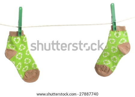 Two recycle print child socks hang on clothesline, environmental energy conservation theme - stock photo