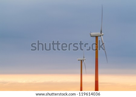 Two red and orange wind turbines during sunset - stock photo