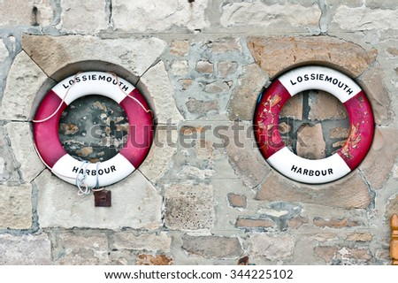 Two red and white emergency flotatation devices at Lossiemouth harbour in Scotland - stock photo