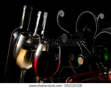 Two red and white wine glasses with bottles and wrought iron rack