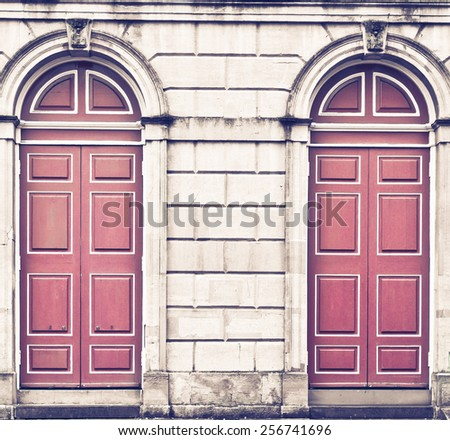 Two red arched doors in a large stone wall in retro tones - stock photo
