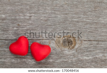 Two red candy hearts on wooden background - stock photo