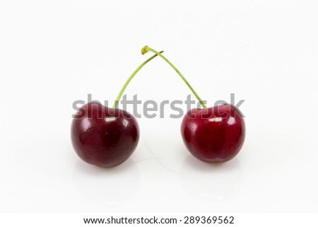 Two red cherry fruit on white background
