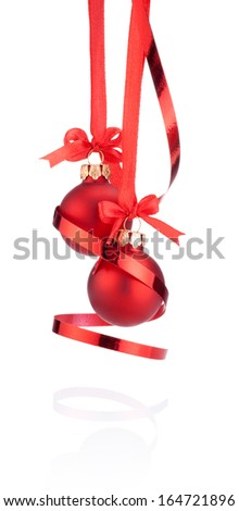 Two Red Christmas ball hanging with ribbon bow and curling paper Isolated on white background