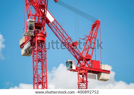 Two Red Construction Tower Cranes Against Blue Sky - stock photo