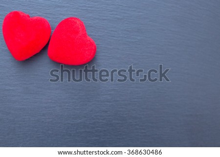 Two red decorative hearts on grey background. Copy space, isolated - stock photo