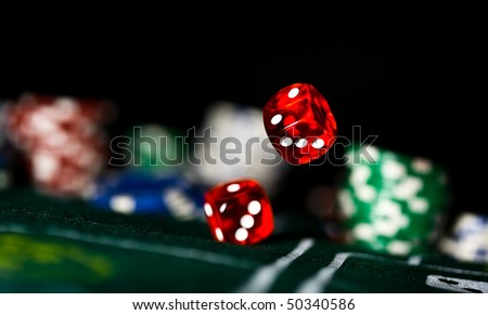 two red dice rolling on felt - stock photo