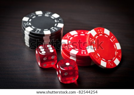 Two red dices and black and red chips. - stock photo