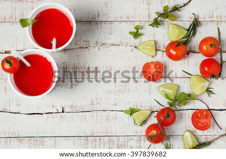 two red drinks with fresh tomato and lime cut on wooden table. Healthy lifestyle, detox background. Copy space - stock photo